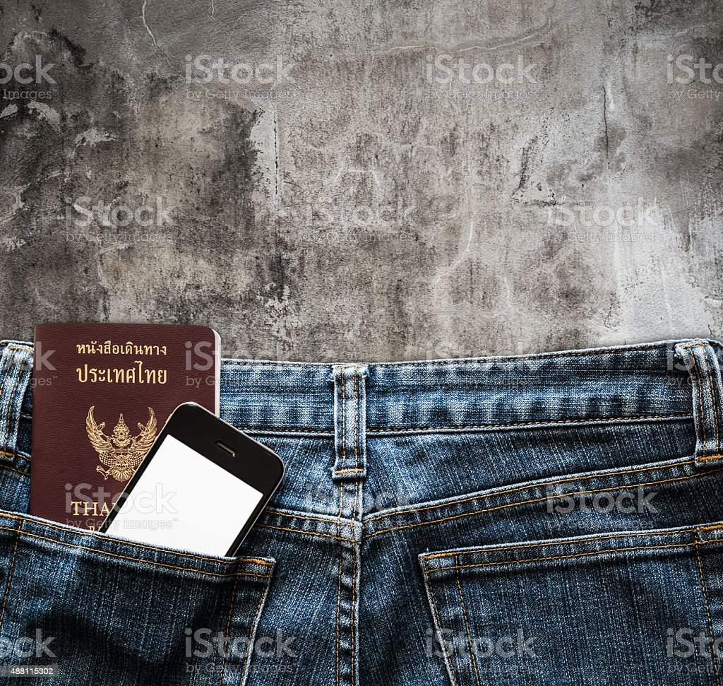 Blue jeans with cell phone and passport background stock photo