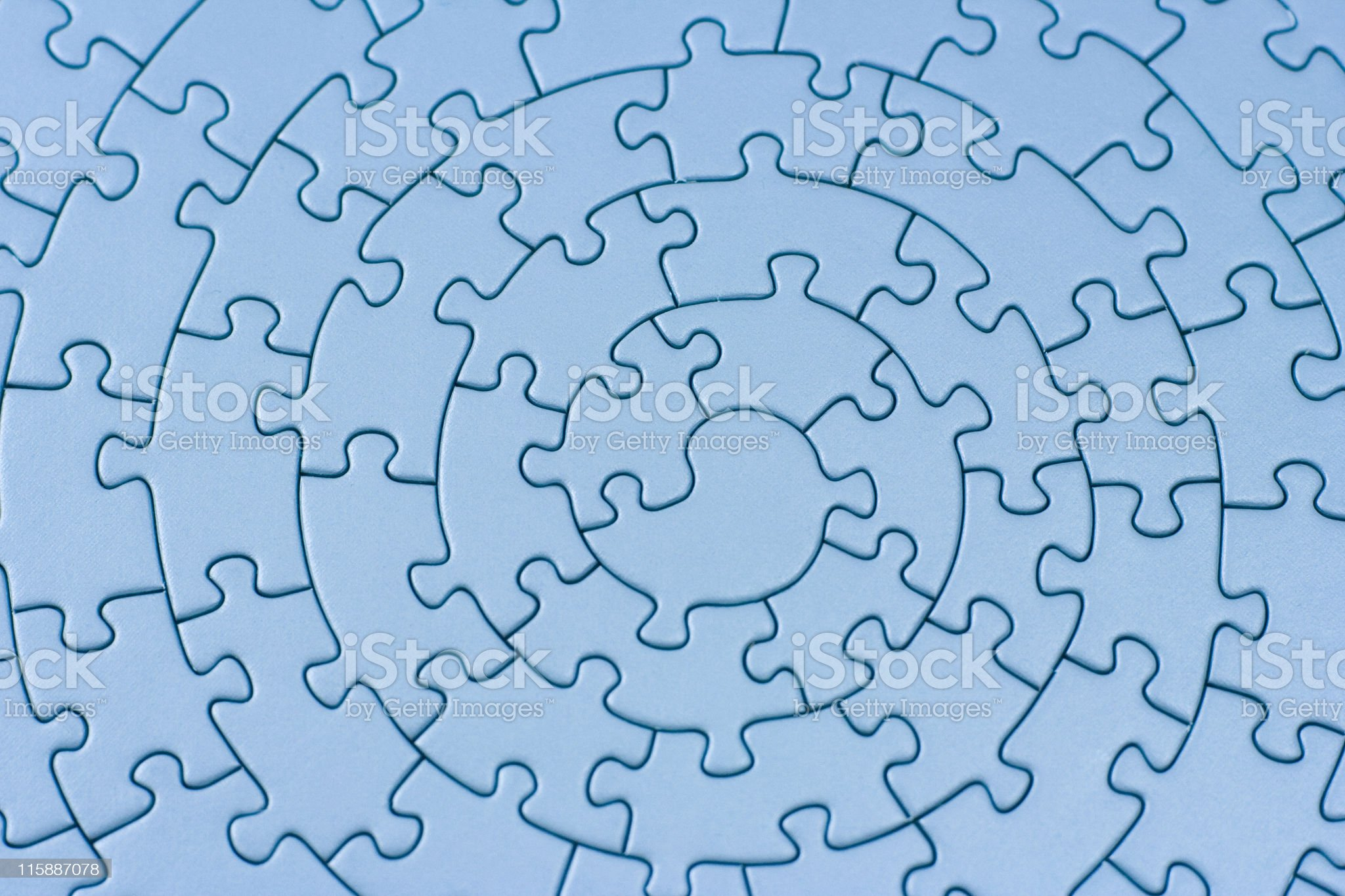 Blue jigsaw puzzle pieces completed in a spiral royalty-free stock photo