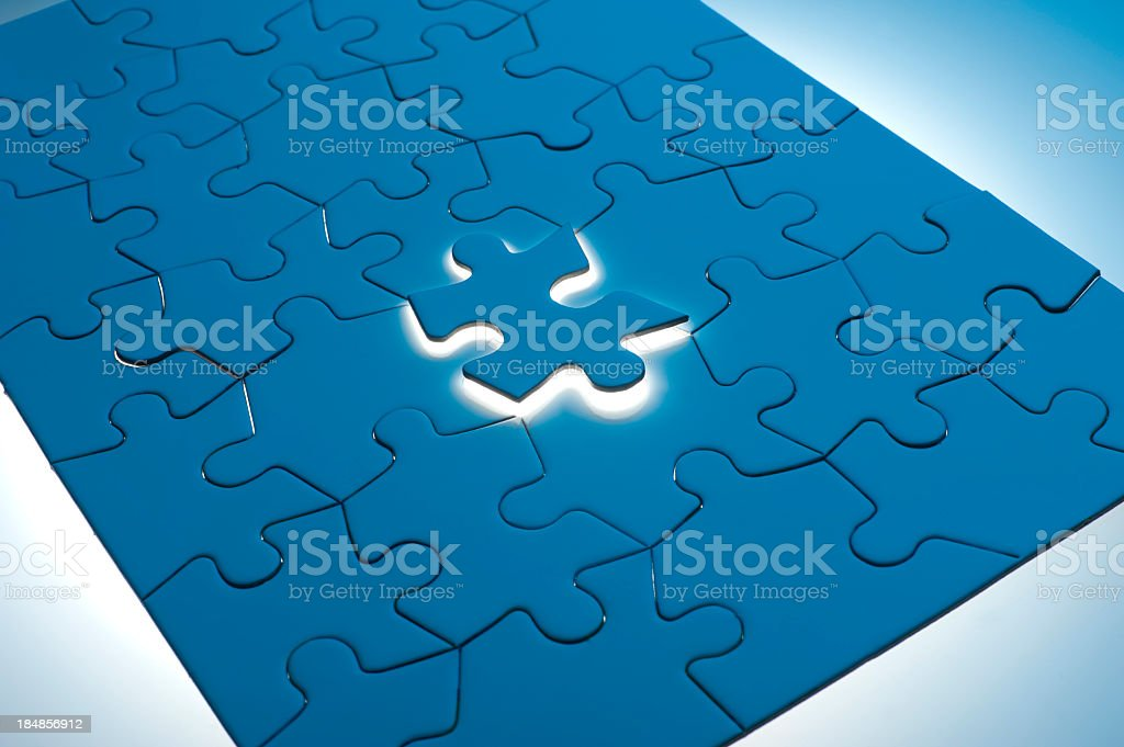 Blue jigsaw puzzle with one piece glowing royalty-free stock photo