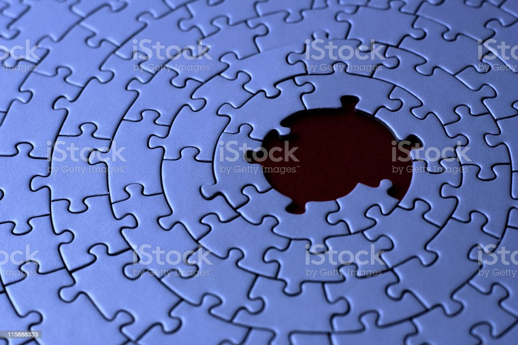 blue jigsaw with missing pieces in the center royalty-free stock photo