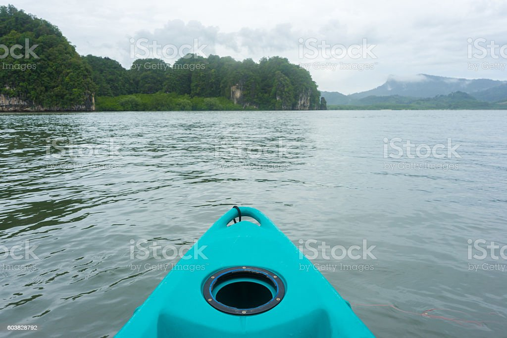 Blue kayak in sea with mountain and cloud background photo libre de droits