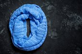 Blue knitted wool circle scarf on a black background