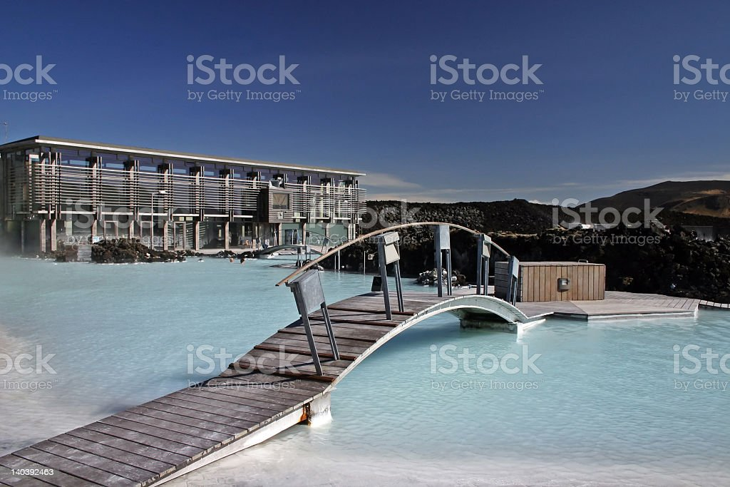 A blue lagoon with a bridge across, overlooking a cityscape royalty-free stock photo