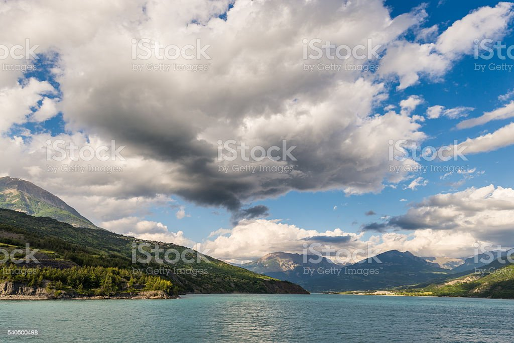 Blue lake amid mountain range and dramatic sky stock photo