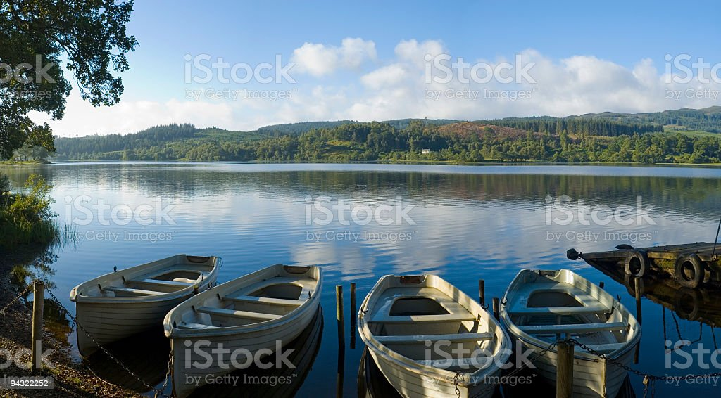 Blue lake, white boats, green hills royalty-free stock photo