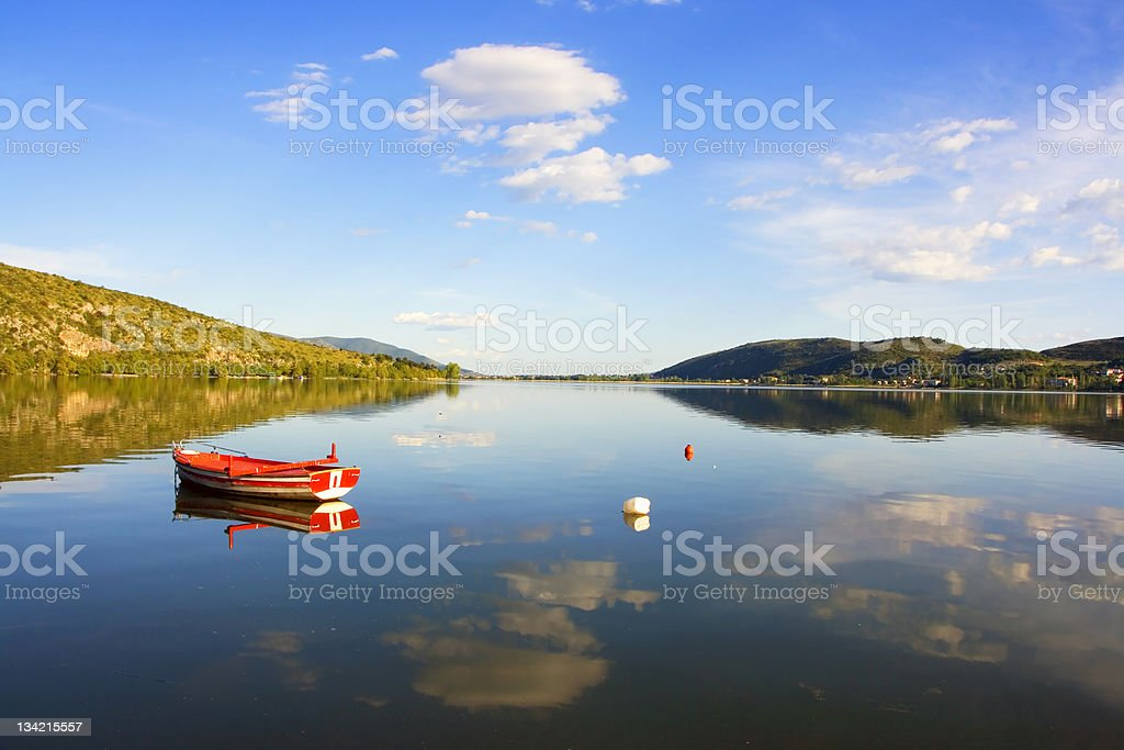 Blue lake,red boat,green hills,white clouds royalty-free stock photo