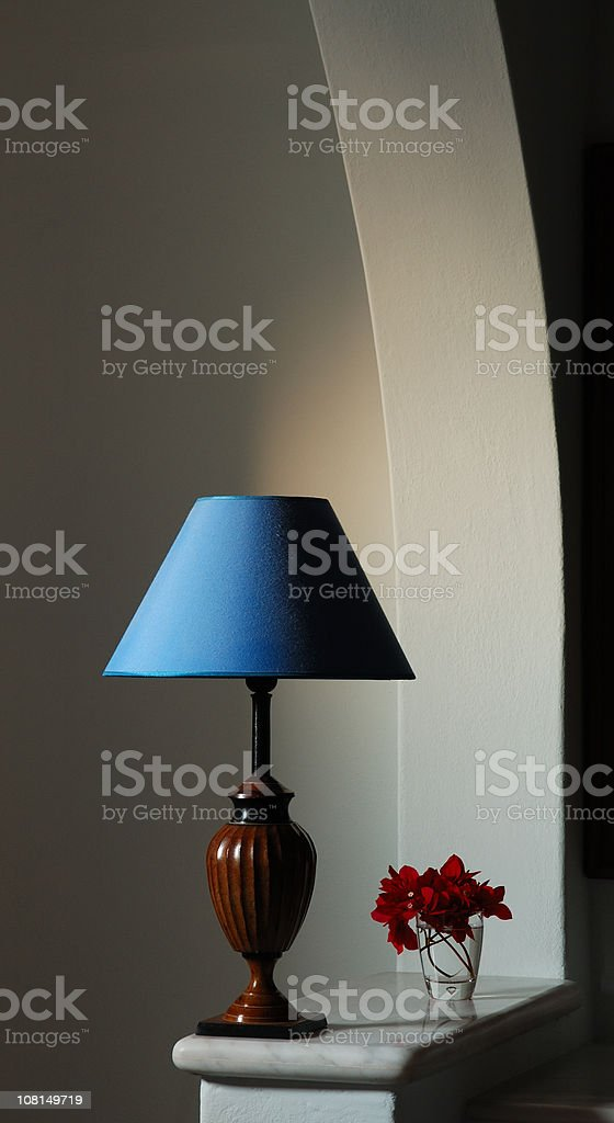 Blue Lampshade with Small Flower Bouquet Under Archway royalty-free stock photo