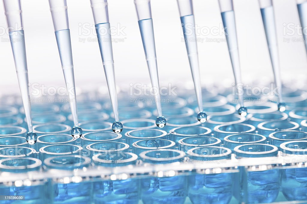 Blue liquid dripping from funnel into test tubes stock photo