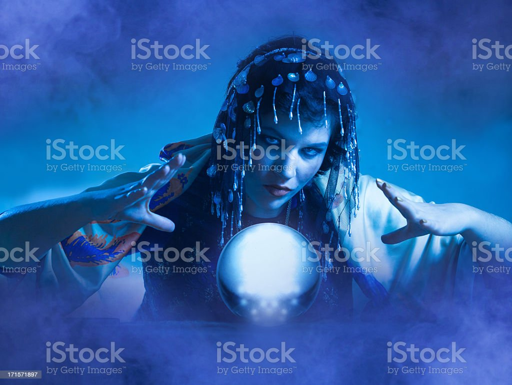Blue lit fortune teller conjuring over a globe stock photo