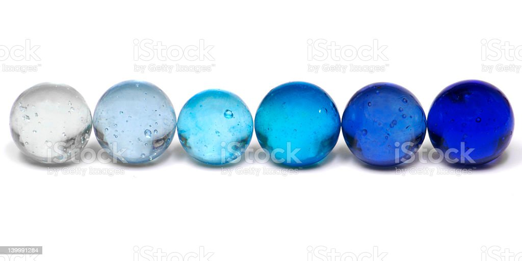 Blue marbles in a graduated row stock photo