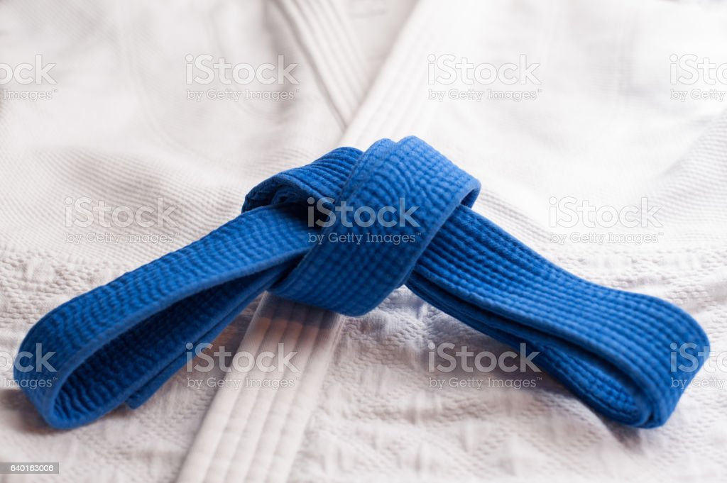 Blue martial arts belt with white kimono in background stock photo