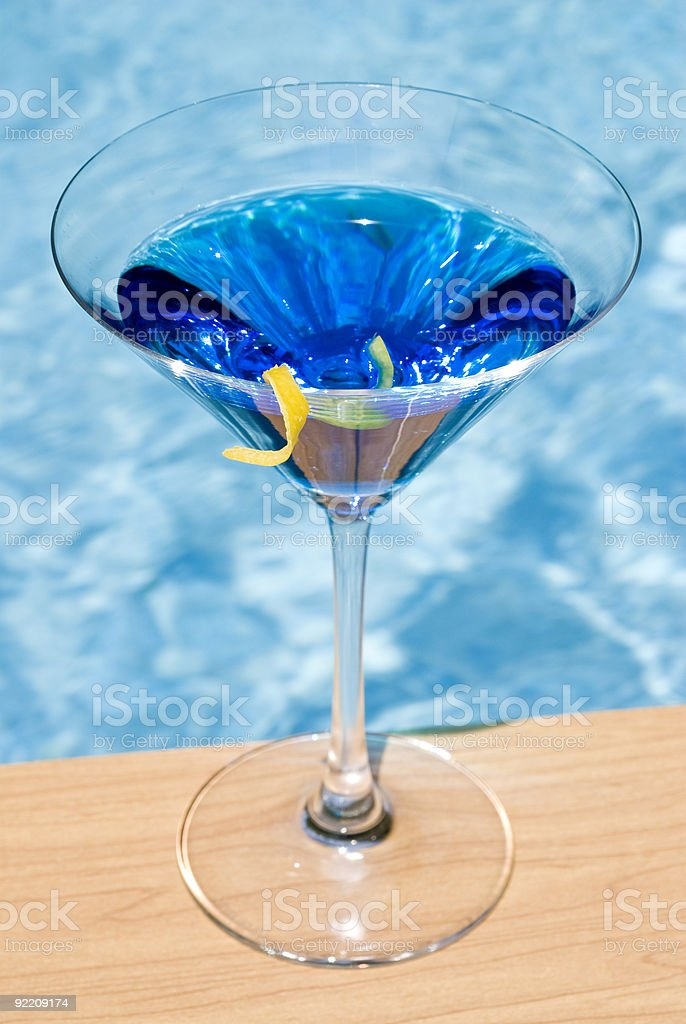 A blue martini by a swimming pool stock photo