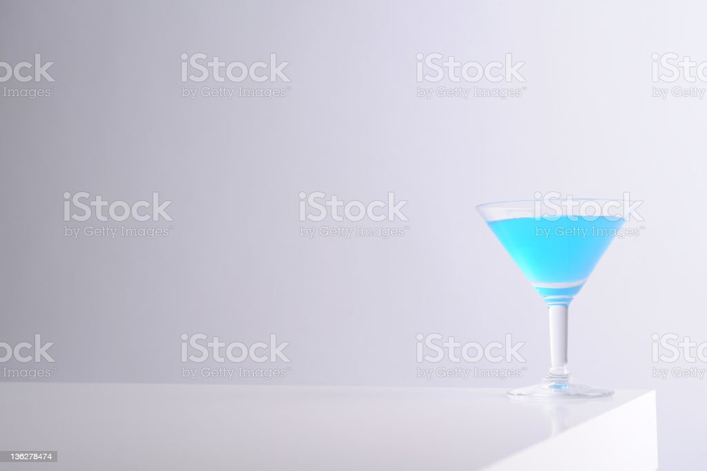 Blue martini glass on white table stock photo