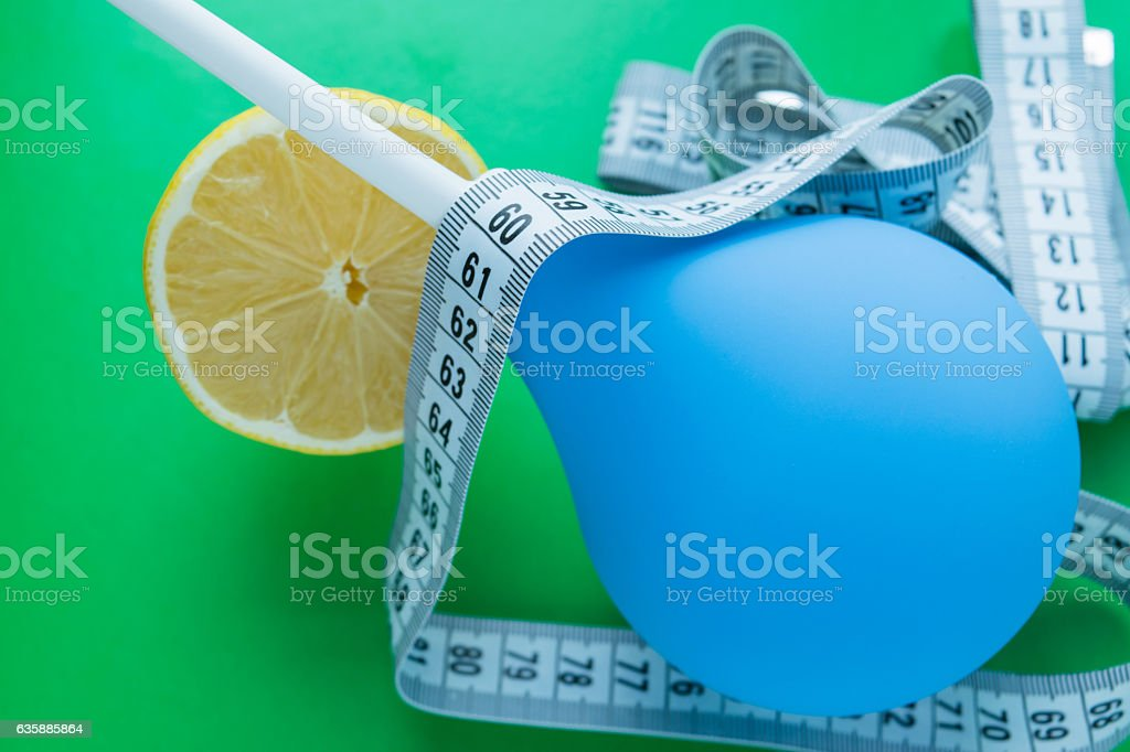 Blue medical enema and fresh lemons, measuring tape stock photo