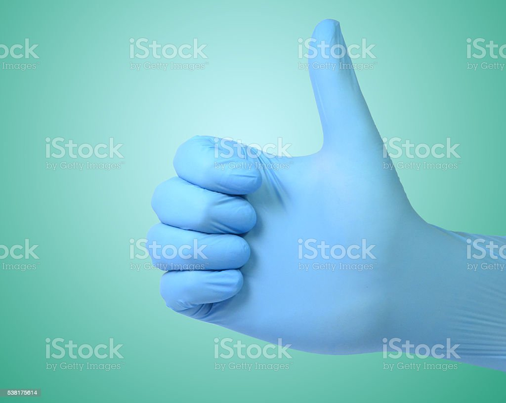 Blue medical gloved fist with thumb up OK stock photo