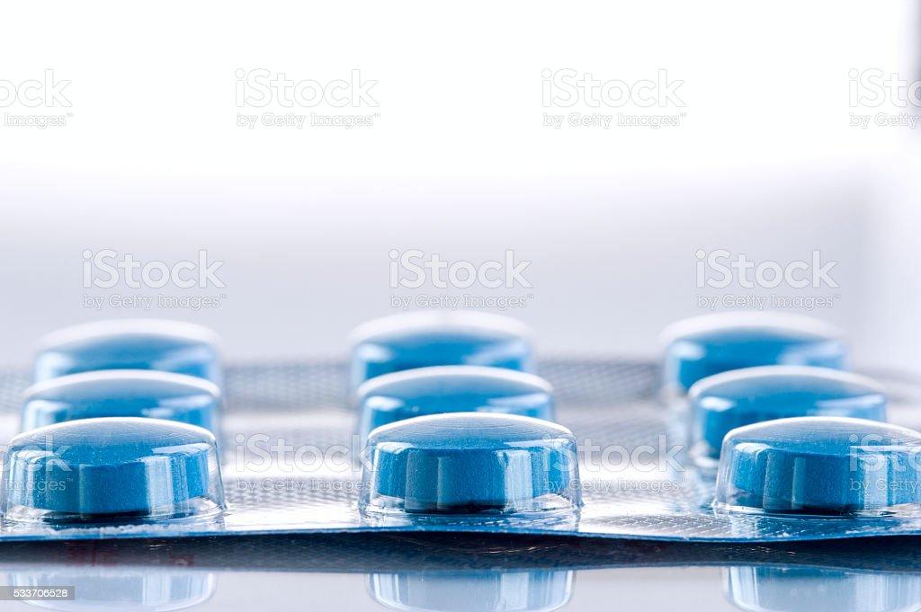 Blue medicine pills on white background. stock photo