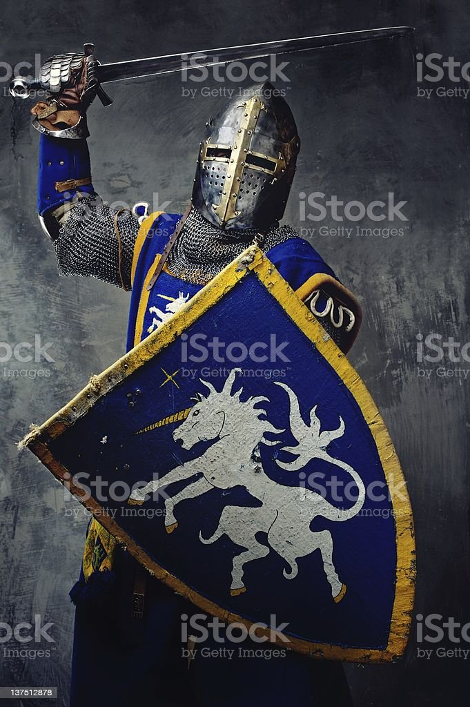 Blue medieval knight with sword raised and shield up stock photo