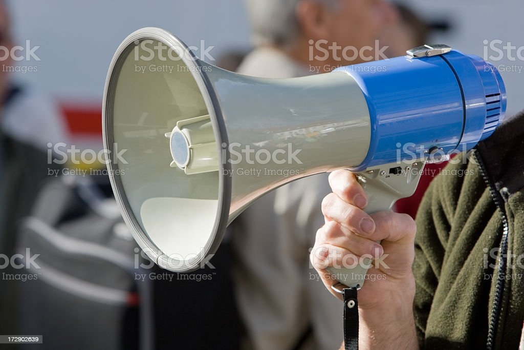 Blue megaphone being held in an action position stock photo