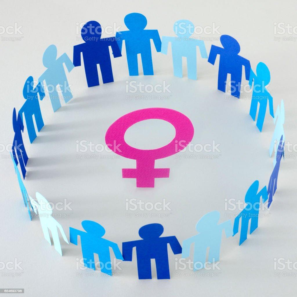Blue men surrounding female symbol stock photo
