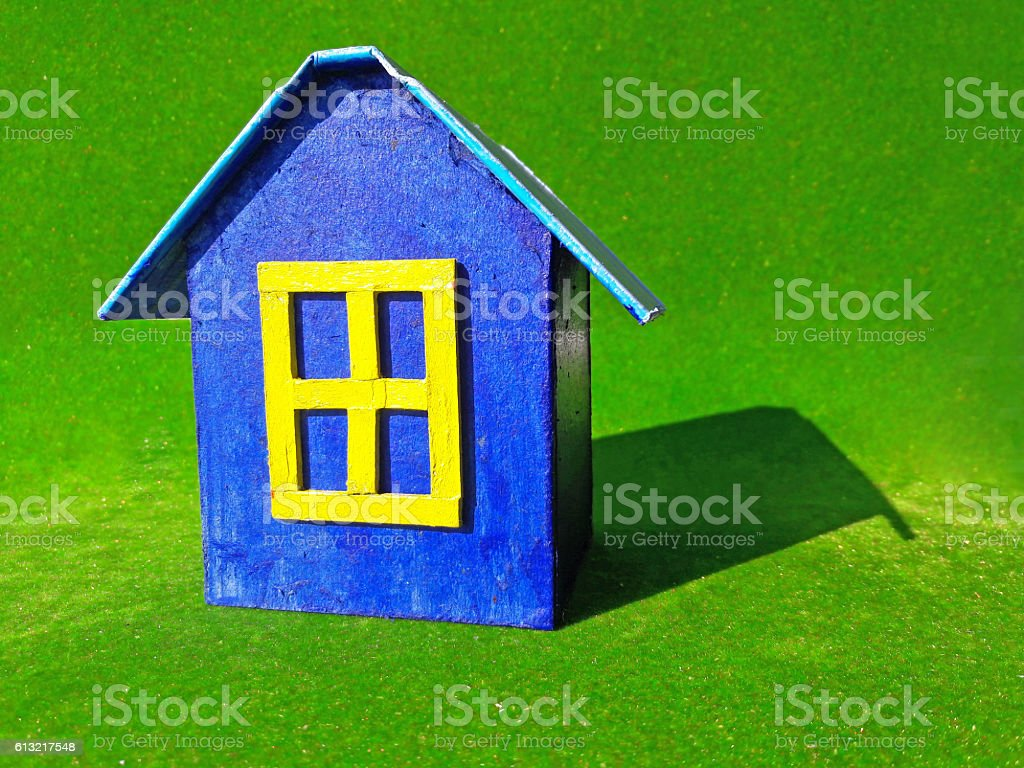 blue model of house as symbol on green background stock photo