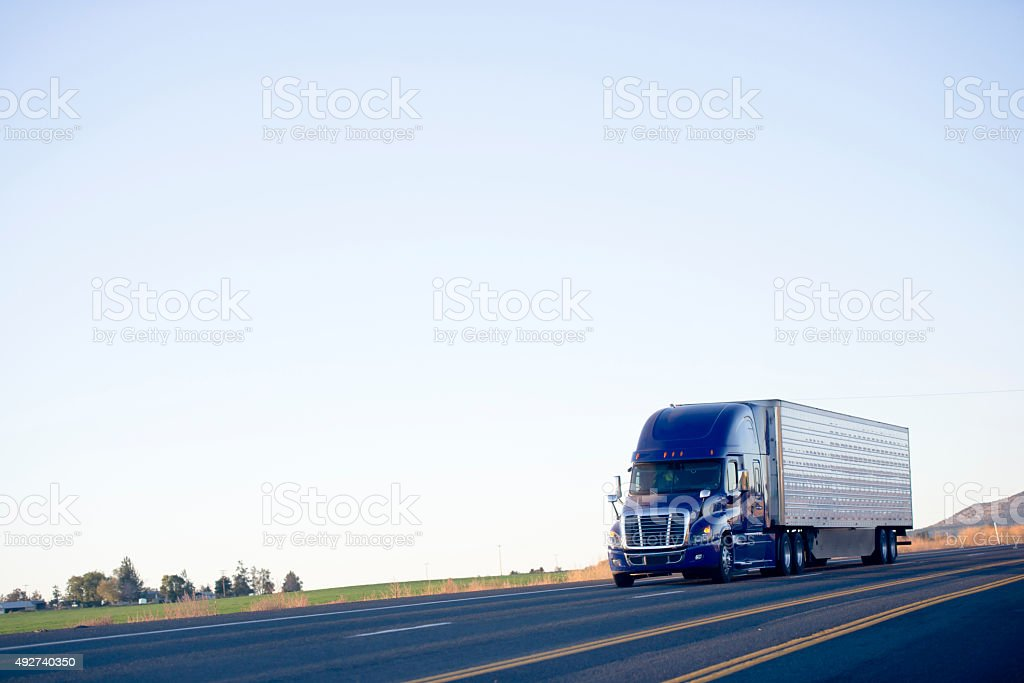 Blue modern semi truck reefer trailer carry cargo on highway stock photo