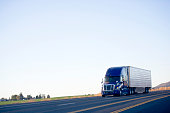Blue modern semi truck reefer trailer carry cargo on highway