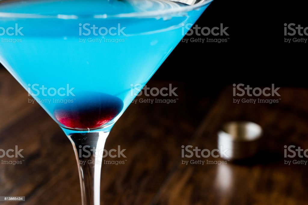 Blue Moon Cocktail with cherry on wooden surface. stock photo