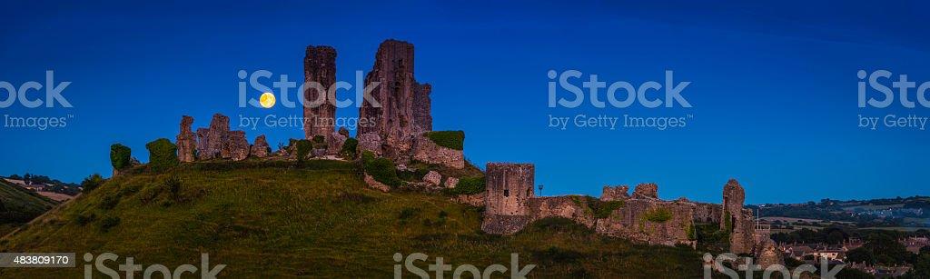 Blue moon rising over castle ruins Corfe Castle Dorset UK stock photo