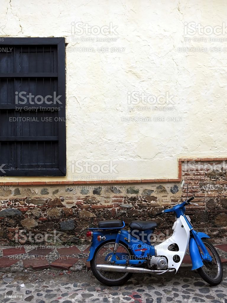 blue moped in front of beige wall of colonial building stock photo