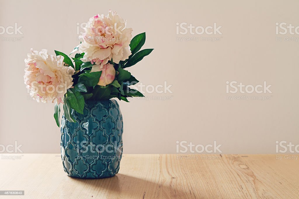 Blue moroccan style vase of large white and pink flowers stock photo