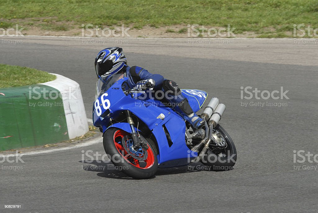 A blue motorcycle racer on a race track royalty-free stock photo