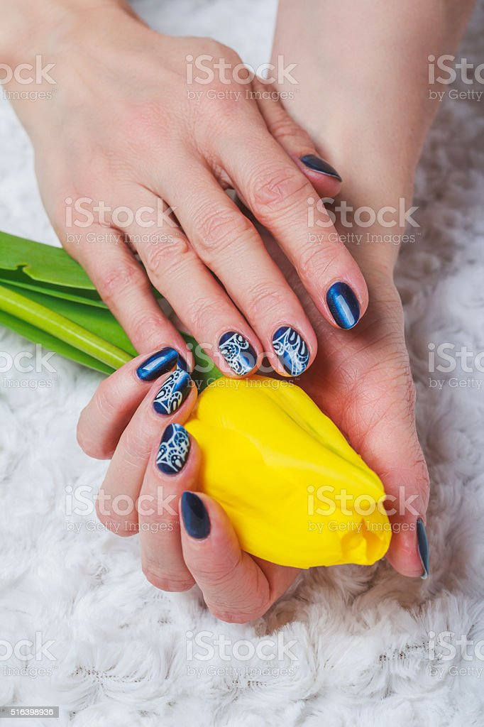 Blue nail art with white lace stock photo