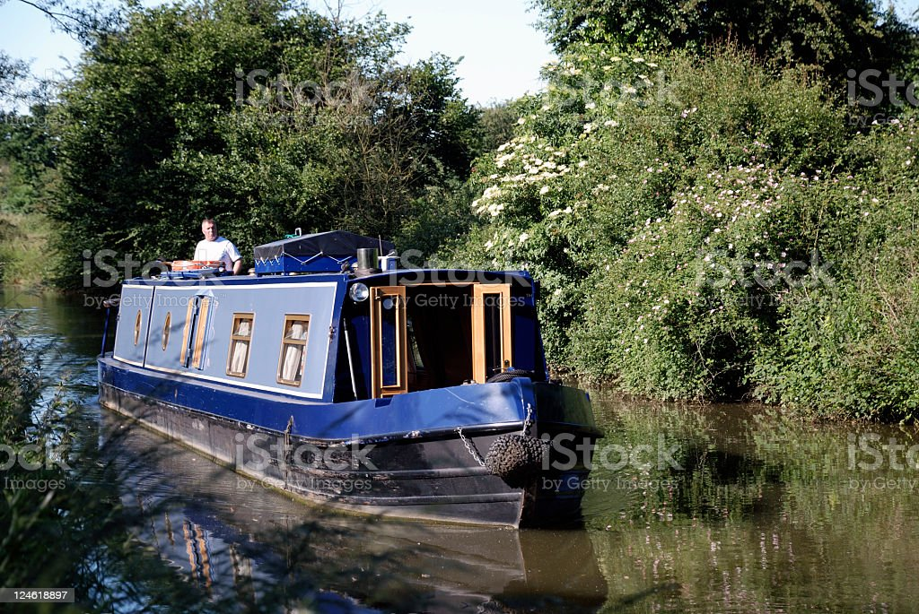 Blue narrow boat cruising on the Oxford canal stock photo