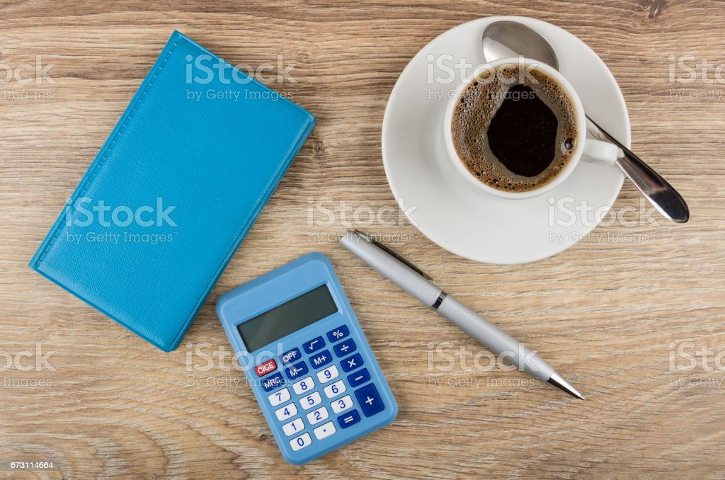 Blue notepad, calculator, ballpoint pen and coffee on table stock photo