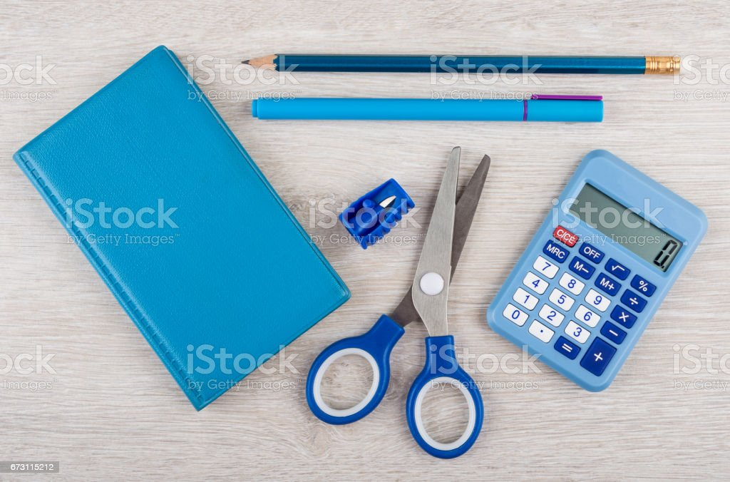 Blue notepad, scissors, calculator and other tools on wooden table stock photo