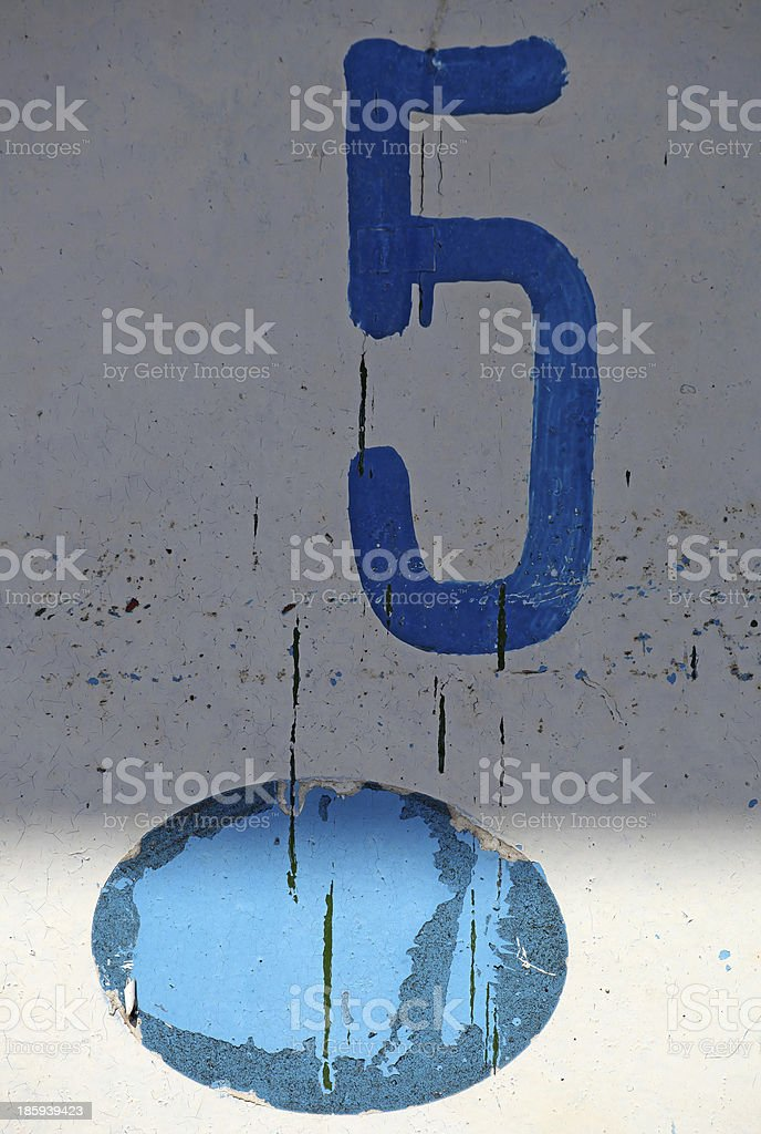 Blue number five painted on white weather worned background royalty-free stock photo