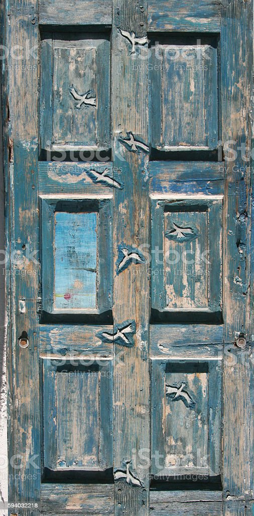 Blue old door carved with seagulls stock photo