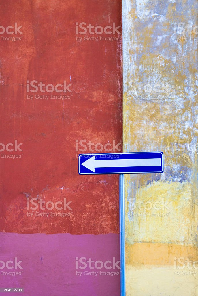 Blue One-Way Sign Against Vibrant Multi-Colored Wall, Rome stock photo