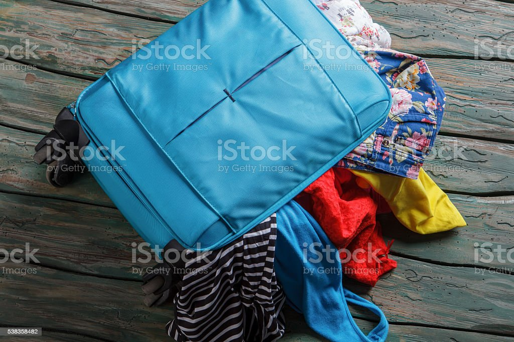 Blue overfilled suitcase. stock photo