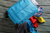 Blue overfilled suitcase.
