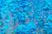 Blue paint over a metallic textured and rusty background.
