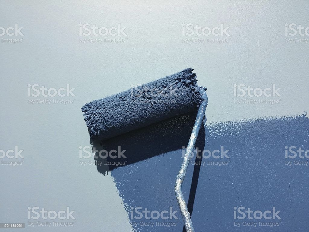 blue paint roller on the wall stock photo