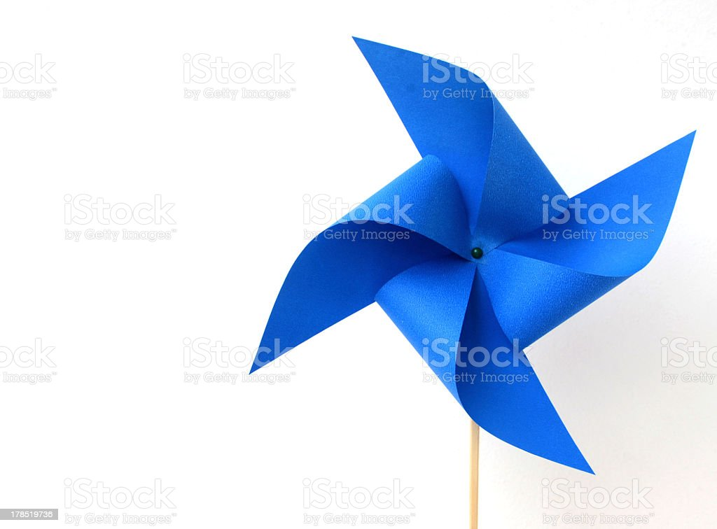 A blue paper windmill on a white background stock photo