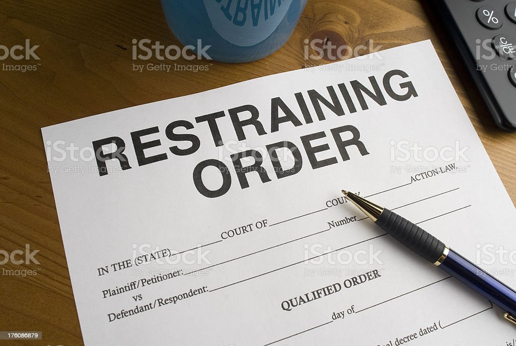 Blue pen laying on a blank restraining order on desk. royalty-free stock photo