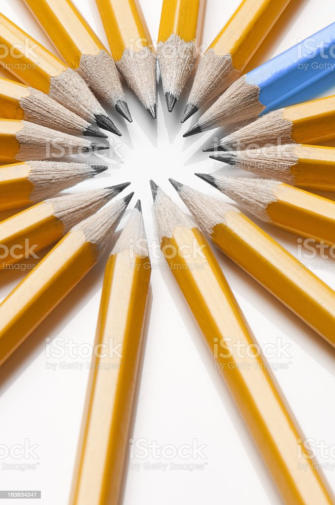 Blue pencil stands out from circle of yellow pencils royalty-free stock photo