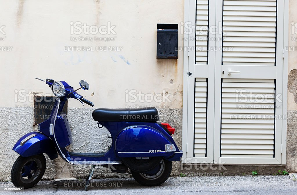 Blue Piaggio Vespa PX125 scooter parked outside Sicilian house. stock photo