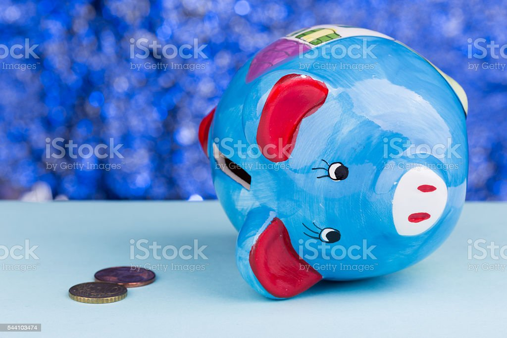 Blue piggy bank on its side: tight money stock photo