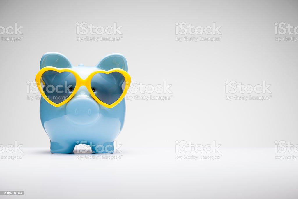 Blue Piggy Bank with Heart Shaped Sunglasses stock photo