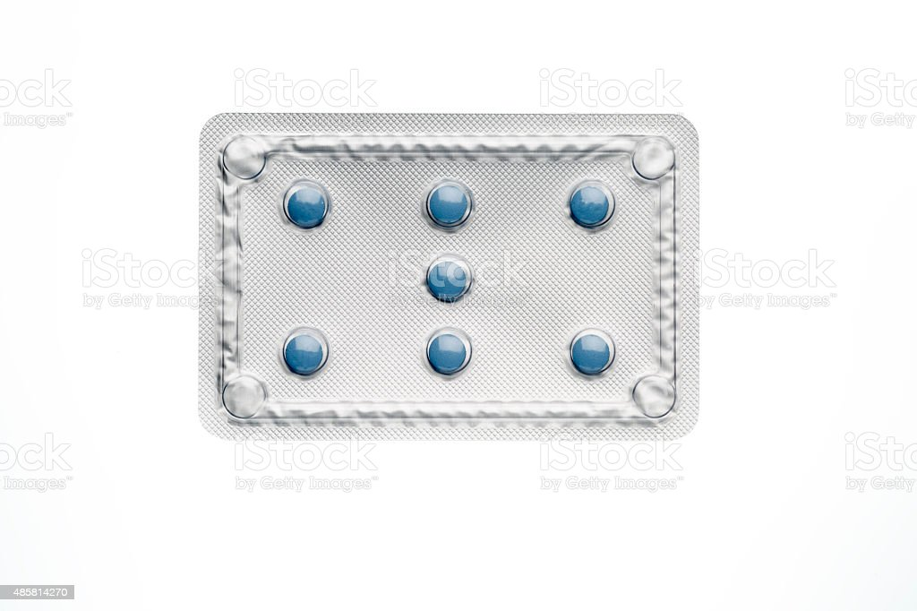 Blue pills in blister package isolated on white background stock photo
