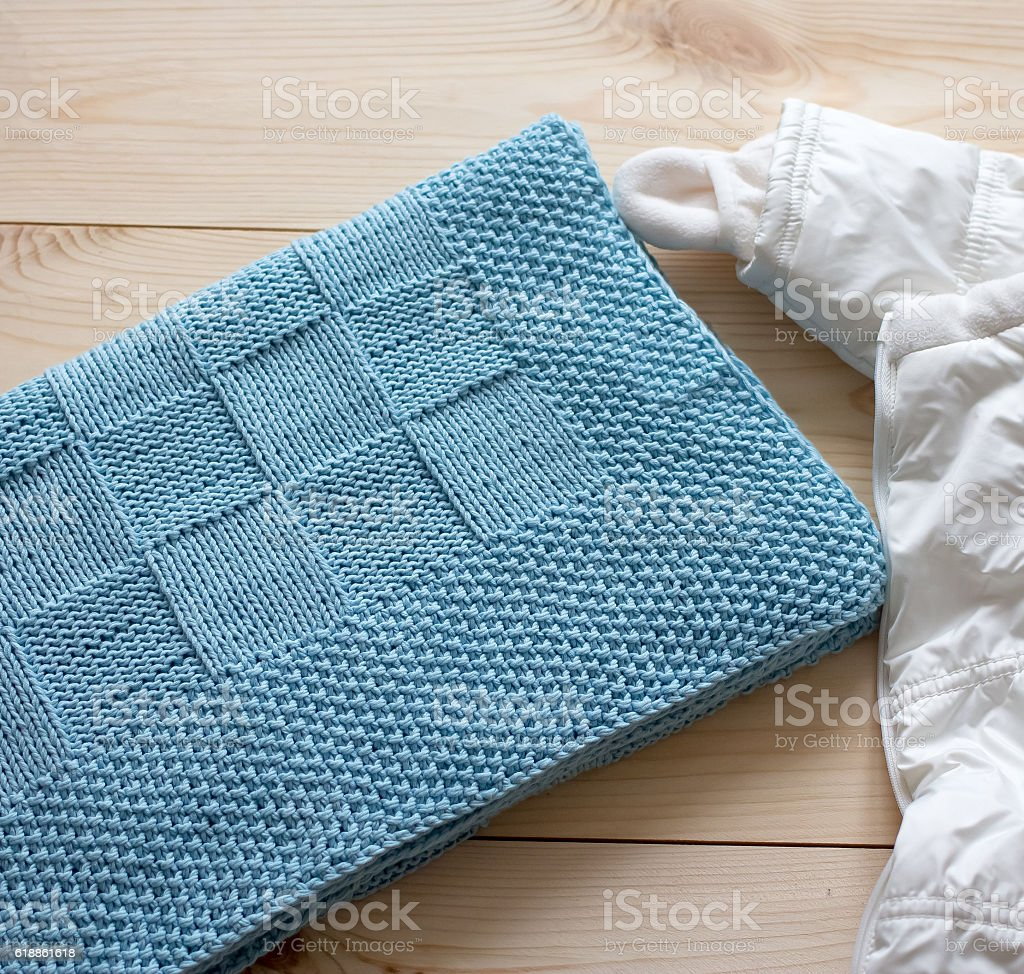 Blue plaid knitted by hand next to the white rompers stock photo